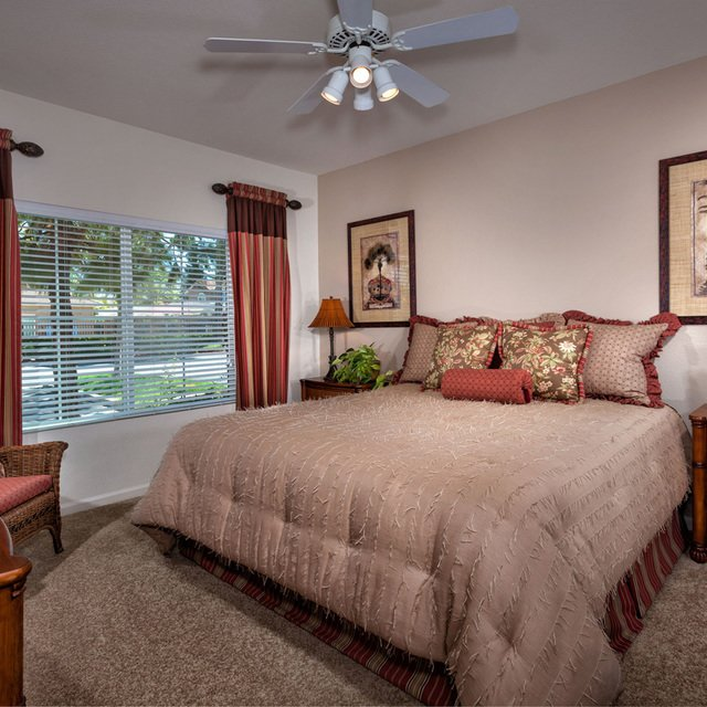 Carmel at Woodcreek West Apartments - Bedroom with tan sheets