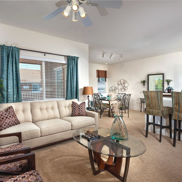 Carmel at Woodcreek West Apartments - Living space with clear coffee table