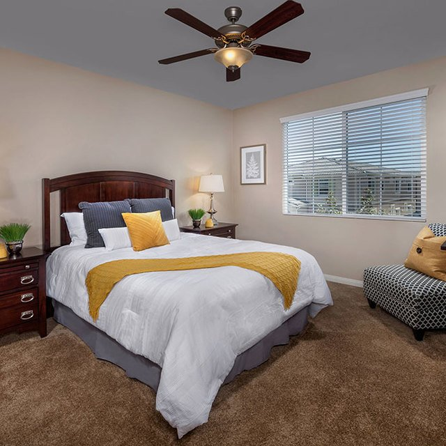 Homecoming at the Preserve Apartments - Bedroom with striped couch